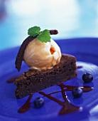 Piece of chocolate cake with orange ice cream & blueberries
