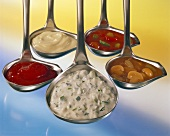 Various sauces in ladles