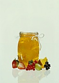 Orange jelly in glass, surrounded by berries & orange slice