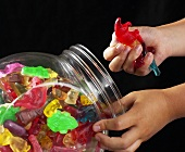 Children's hands taking fruit gum out of glass container