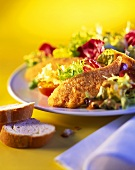 Mixed salad leaves with fried chicken; white bread
