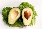 Two avocado halves on lettuce leaves