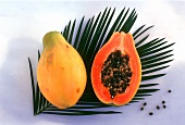 Whole and half papaya on palm leaf