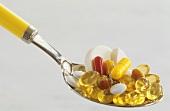 Various vitamin pills on spoon