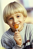 Small boy licking lollipop