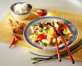 Chicken & vegetables cooked in wok; rice, ginger; chili sauce