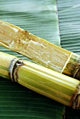 Sugar cane on palm leaves, a piece cut off