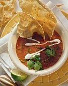 Tomato soup with sour cream; tortilla chips; lime