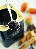Tea leaves on spoon above tea caddy