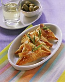 Cheese and herb triangles with sesame; olives; wine (Greece)