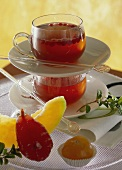 Fruit tea with cranberries in glass cups; candied fruit