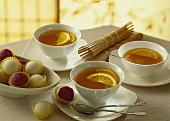 Three cups of tea with slices of orange; chocolate truffles