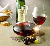 Red wine in glass, carafe and bottle; red grapes; baguette