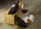 Red wine bottle in wooden crate; red wine glass; red grapes