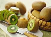 Fresh kiwi fruits in basket and on chopping board