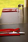 Einfach gedeckter Tisch mit Besteck und roten Servietten