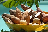 Potatoes, sweet potatoes and yam in yellow bowl