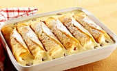 Crepes with vanilla cream and raisins in baking dish