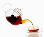 Pouring tea from glass teapot into cup