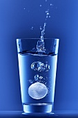 Brausetablette fällt in ein Wasserglas