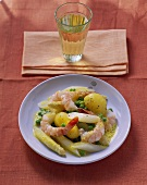 Shrimps with saffron whip and vegetables; glass of white wine