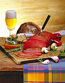 Beef ham on chopping board; mushrooms, bread, beer