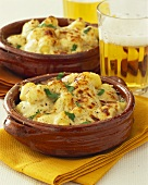 Gnocchi with cheese sauce; glass of beer