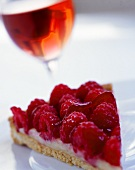 Piece of raspberry flan and glass of rosé wine