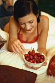 Young woman holding bowl of red cherries