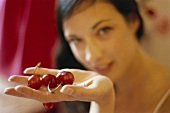 Young woman holding red cherries in her hand