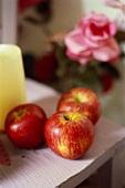 Three fresh apples on table; pink rose