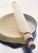 Unrolling shortcrust pastry over tart tin