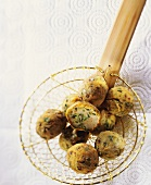 Spicy chicken rissoles on slotted spoon