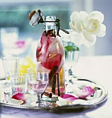 Rose water in bottle and glass on tray