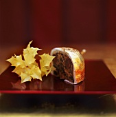 Small mince pie with gold and silver leaf, a piece cut off