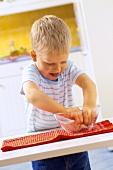 Small boy kneading pizza dough