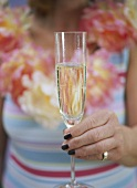 Woman in summer dress holding glass of champagne