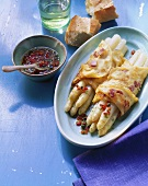Crepes with white asparagus, ham and pepper and caper sauce