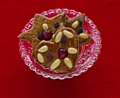 Gingerbread with almonds and candied cherries on plate