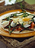 Pizza base with raw ham, fried egg and green asparagus