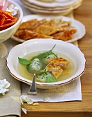 Green wedding soup with herb dumplings and ham dumplings