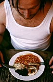 Man in vest eating beans with sausage and fried egg