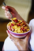 Pregnant woman eating cornflakes with strawberries