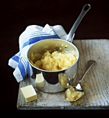 Mashed potato in pan; piece of butter; apple puree on spoon