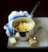 Kartoffelpüree im Kochtopf; Butterstück; Apfelmus auf Löffel