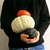 Man in black pullover holding three different pumpkins
