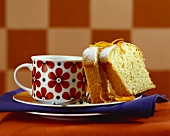 Two slices of coconut cake with orange beside coffee cup