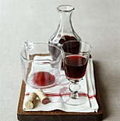 Red wine in glass, carafe and measuring jug on chopping board
