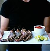 Person serviert Tiger Prawns mit Tomatensauce und Limetten