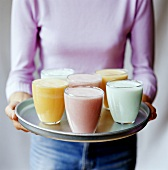 Woman serving tray of different smoothies